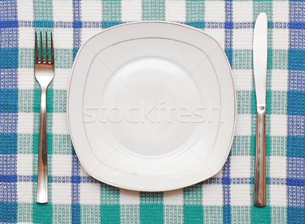 White empty plate with fork and knife on checkered tablecloth Stock photo © inxti
