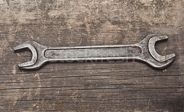 Old corroded spanner over battered wood, grungy style  Stock photo © inxti