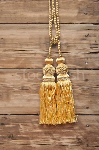 Gold rope with curtain tassel against wooden wall Stock photo © inxti