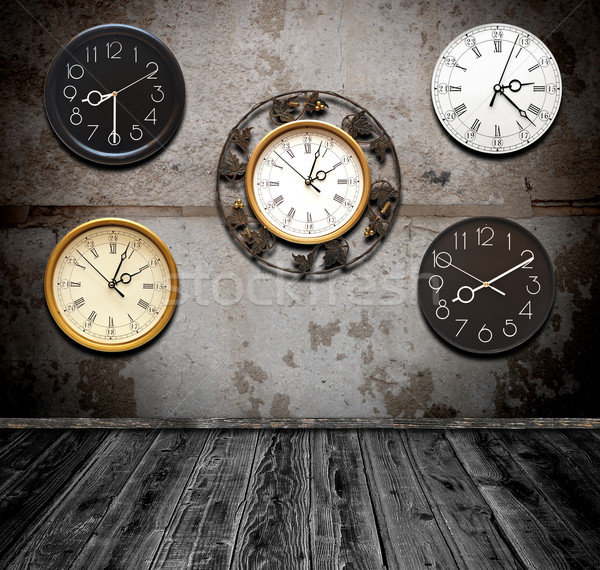 collection of wall clock against an wall in old room  Stock photo © inxti