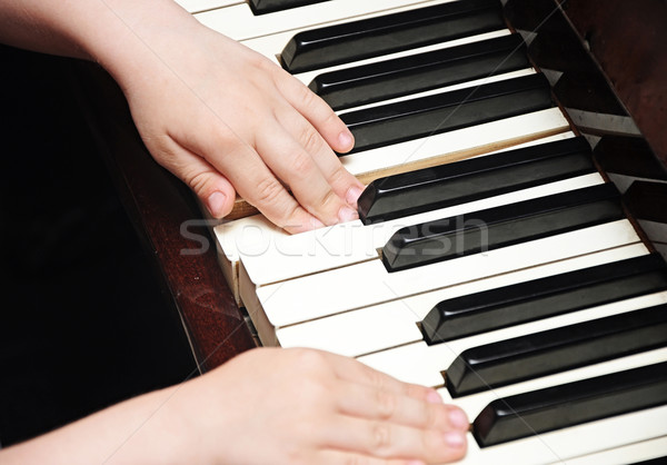 child's hands playing the piano Stock photo © inxti