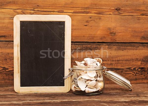 Seashells in a jar on wooden background  Stock photo © inxti