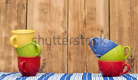 Colorful coffee cups on stripe tablecloth over wood background  Stock photo © inxti