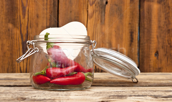 red chilly peppers in glass jar with cardboard heart on wood bac Stock photo © inxti