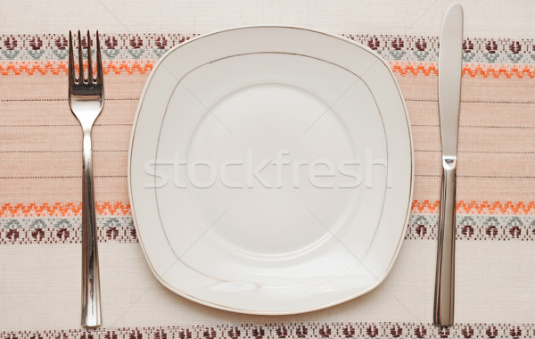 Stock photo: Knife, white plate and fork on tablecloth