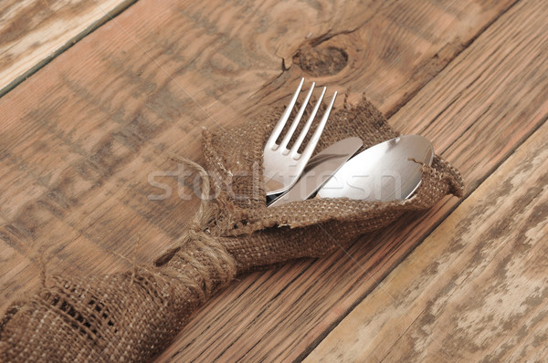 knife and fork in rough old sacking over wood Stock photo © inxti