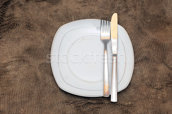 empty white plate fork and knife on brown sacking texture Stock photo © inxti