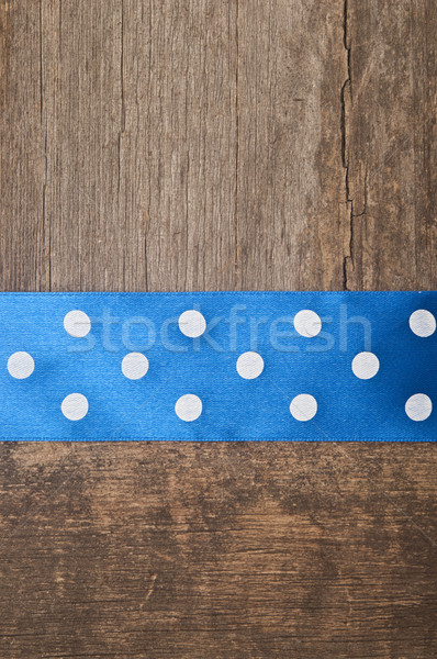 Wooden background with blue polka-dot ribbon Stock photo © inxti