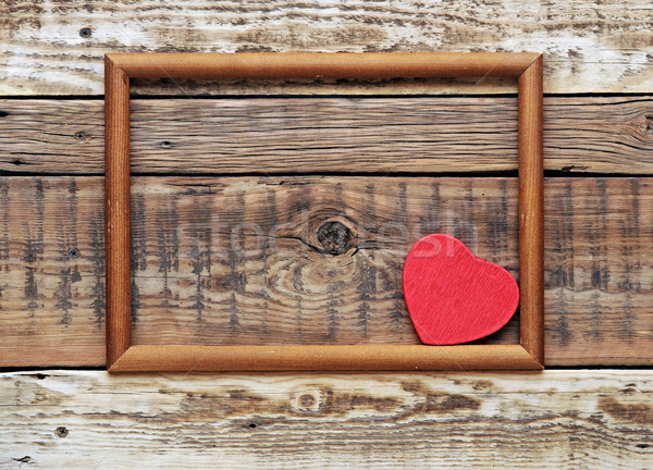 A red heart in an old wooden frame on an old rough wall.  Stock photo © inxti