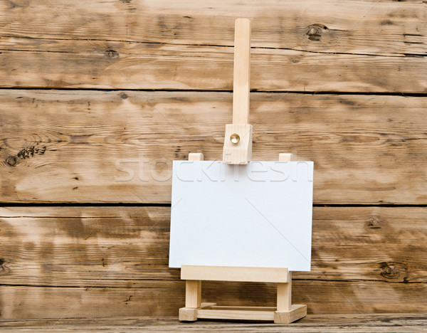 Wooden easel with clean paper on old wooden table Stock photo © inxti