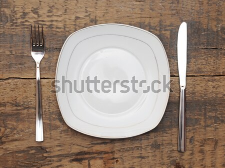 Empty dish, knife and fork and brown napkin on old wood table  Stock photo © inxti