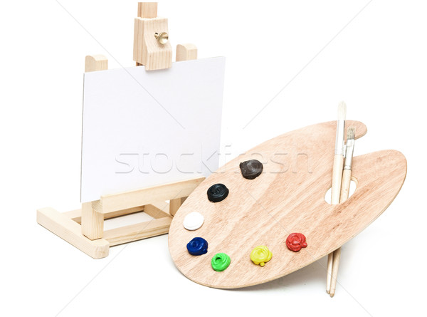 Wooden easel with clean paper and wooden artists palette loaded  Stock photo © inxti