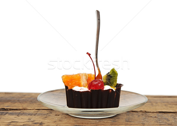 Stock photo: Chocolate cupcake with a cherry and tropical fruit on glass dish