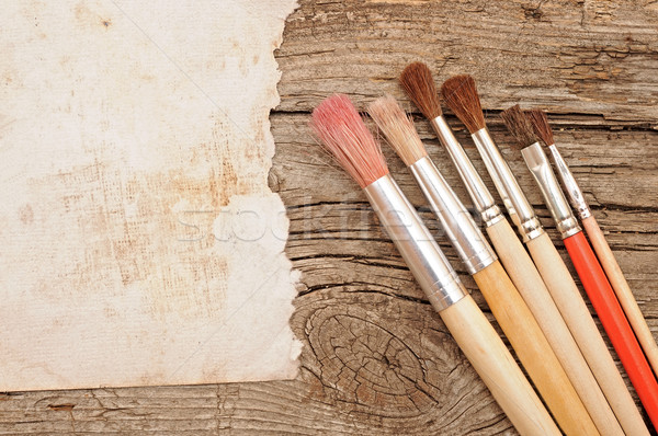 Paint brushes on old wooden background with blank vintage paper Stock photo © inxti