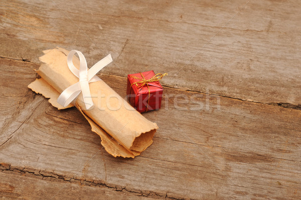 Red box with an old scroll on wooden background Stock photo © inxti