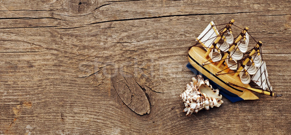 Sailing vessel and sea shell on wood background Stock photo © inxti