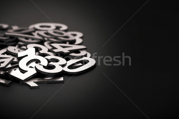 closeup image with pile metal numbers on black background, space Stock photo © inxti