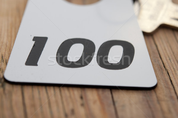 Hotel suite key with room number 100 on wood table  Stock photo © inxti
