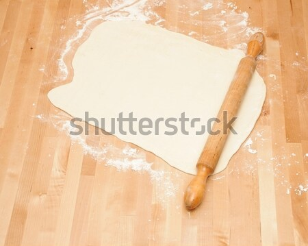 Classic wooden rolling pin with freshly prepared dough and dusti Stock photo © inxti