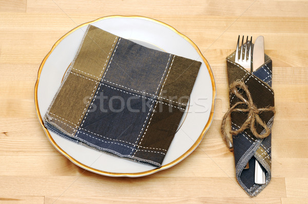 knife and fork in textile napkin on wooden table Stock photo © inxti