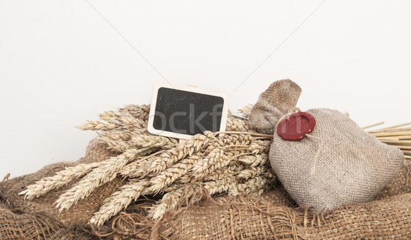 Ears of wheat and sack of wheat grains on brown wooden backgroun Stock photo © inxti