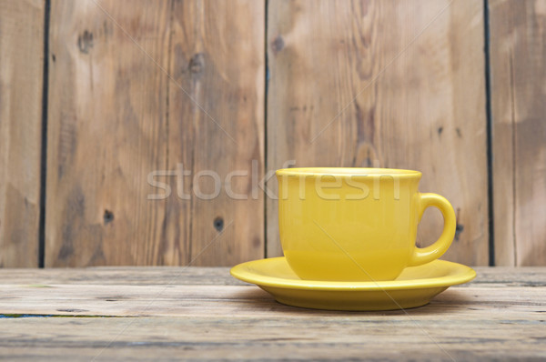 Yellow coffee cup and saucer on a wooden table Stock photo © inxti