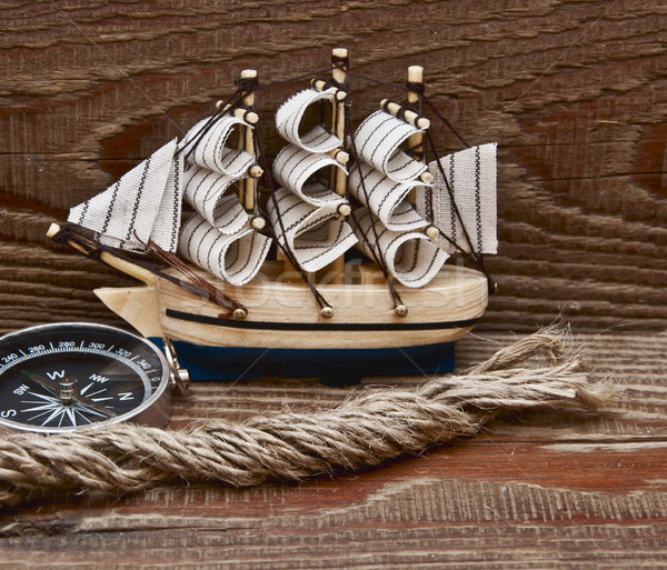 compass, rope and model classic boat on wood background Stock photo © inxti