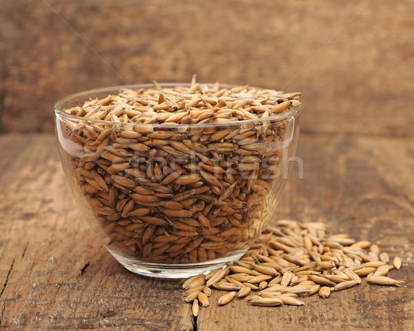closeup oats heaped in a glass cup on wooden table Stock photo © inxti