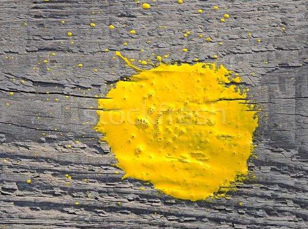 Yellow paint splashed over old wooden background Stock photo © inxti
