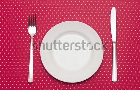 Empty white dinner plate with utensils on fun red polka dot tabl Stock photo © inxti