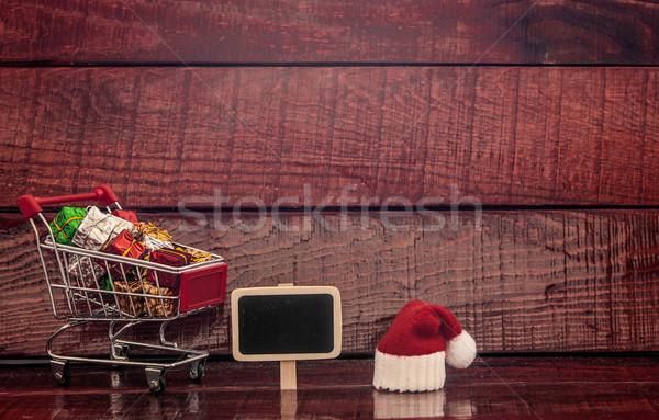 Bevásárlókocsi tele színes ajándékdobozok üres tábla fából készült Stock fotó © inxti