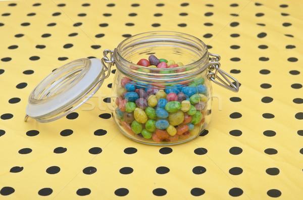 Colorful candies in glass jar on polka dot napkin Stock photo © inxti