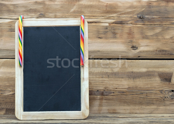 Small blank wooden chalkboard with a festive candy cane for your Stock photo © inxti
