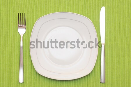 Empty dish, knife and fork and green napkin on wood table Stock photo © inxti