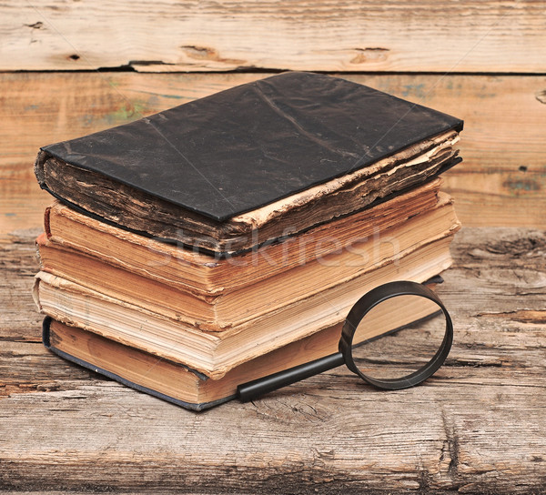 Stack of antique books with magnifying glass on wooden table Stock photo © inxti