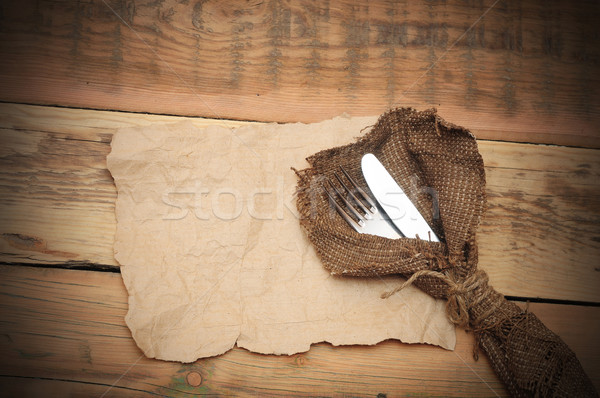 knife and fork in rough old sacking on blank paper over wood Stock photo © inxti