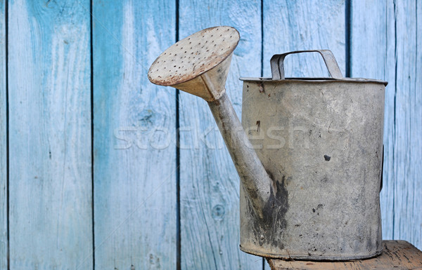 old watering can on wooden background Stock photo © inxti