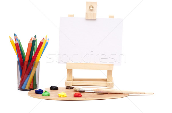 Wooden easel with clean paper and artist color palette Stock photo © inxti