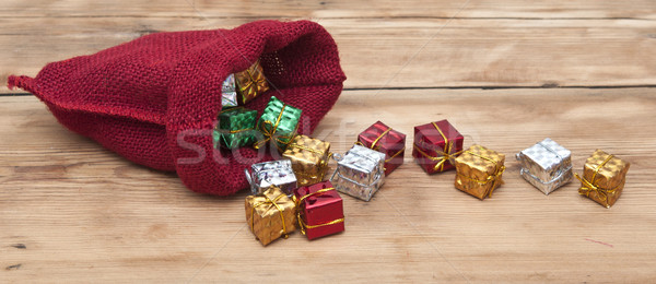 Colorful gift boxes with ribbons and bows, and red sack on woode Stock photo © inxti