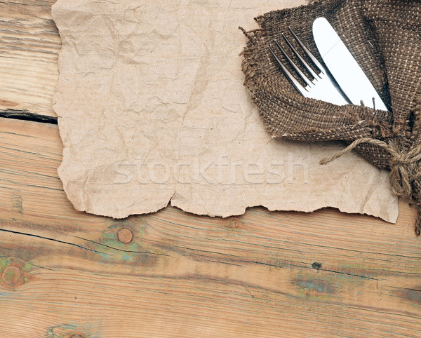 A place setting with silver fork and knife on old sacking textur Stock photo © inxti