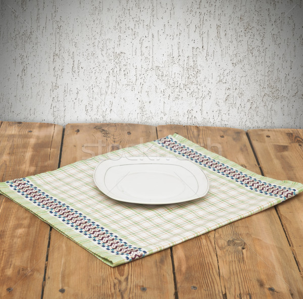 Empty plate on tablecloth on wooden table over grunge background Stock photo © inxti