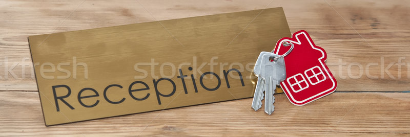 Symbol of the house with silver key on wooden reception desk  Stock photo © inxti