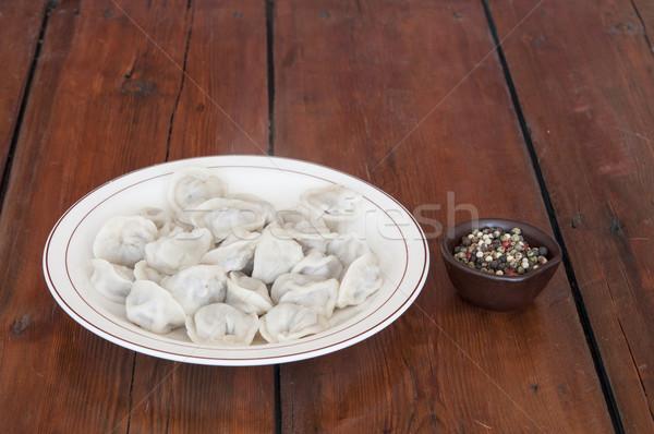Homemade meat dumplings - russian pelmeni on plate Stock photo © inxti