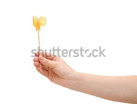 Sweet cockerel on stick in hand isolated on white  Stock photo © inxti