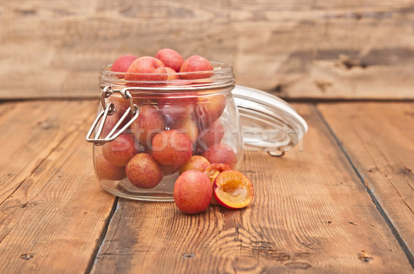 freshly picked plum in glass jar on old wooden table Stock photo © inxti