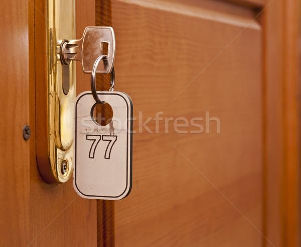 Door handles on wood wing of door and key in keyhole with number Stock photo © inxti
