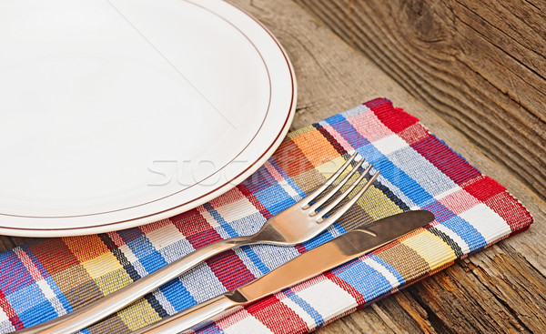 Empty plate with fork and knife on wooden table Stock photo © inxti
