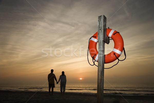 Сток-фото: пару · , · держась · за · руки · пляж · силуэта · смотрят · закат