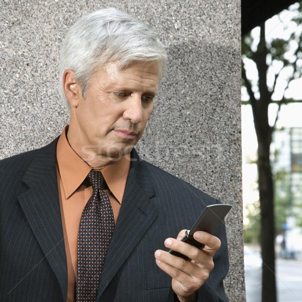 üzletember sms üzenetküldés kaukázusi középkorú lefelé néz mobiltelefon Stock fotó © iofoto