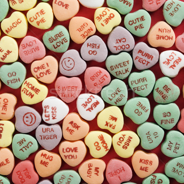 Stock photo: Candy hearts on red.